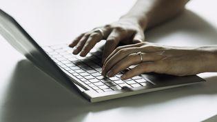 Une femme travaille sur un ordinateur portable. Photo d'illustration. (ERIC AUDRAS / MAXPPP)