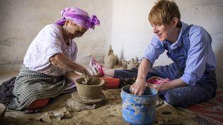 La potière marocaine Aicha Tabiz assise à côté de l'apprentie britannique Kim West, 33 ans, lors d'un atelier de poterie près du village d'Ourtzagh, au pied des montagnes du Rif, le 12 juin 2019. (FADEL SENNA / AFP)