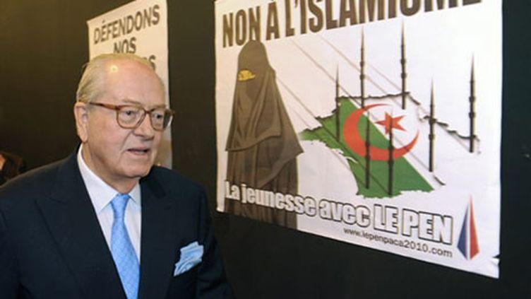 Jean-Marie Le Pen et l'affiche de son parti aux régionales 2010, pour laquelle il est poursuivi (AFP)