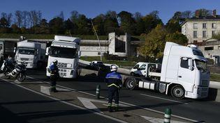 Des policiers encadrent une opération escargotmenée par des forains sur l'A13, le 6 novembre à Saint-Cloud (Hauts-de-Seine). (PHILIPPE LOPEZ / AFP)