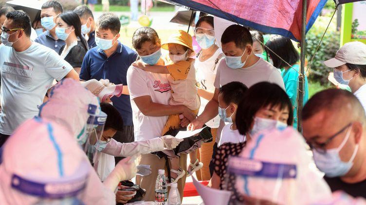Des résidents de Wuhan (Chine) se font tester contre le Covid-19, le 3 août 2021. (STR / AFP)