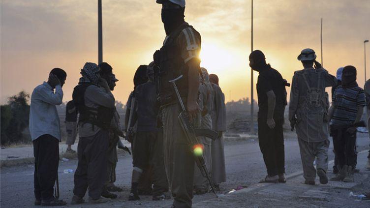 (Des djihadistes de l'Etat islamique en Irak et au Levant (EIIL) à l'entrée de Mossoul © REUTERS)
