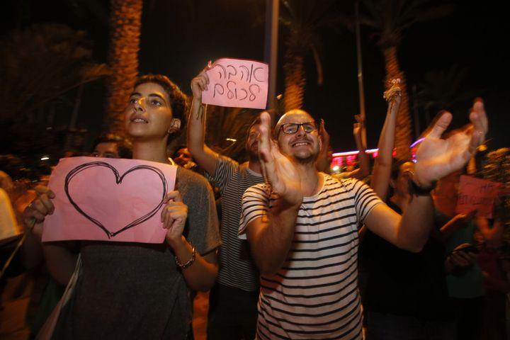 Les supporteurs des mariés ont brandi des pancartes soutenant les deux amoureux. (GALI TIBBON / AFP)