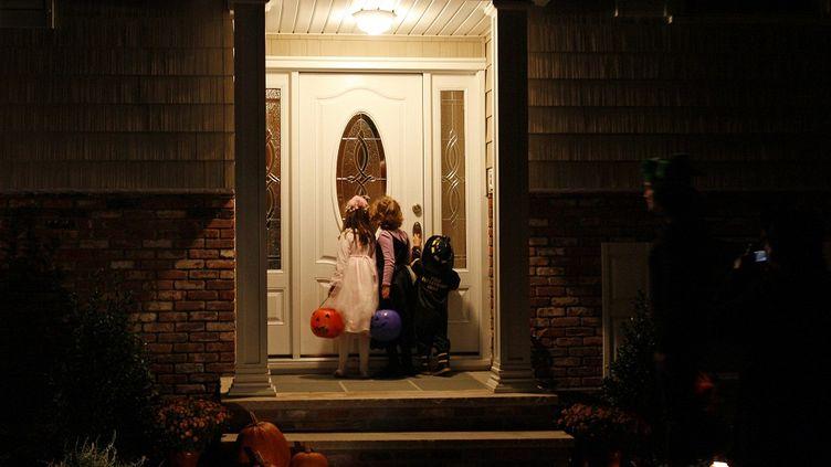 Des enfants sonnent à la porte d'une maison à Nyack, dans la banlieue de New York (Etats-Unis), pour réclamer des bonbons, le 31 octobre 2008. (MIKE SEGAR / REUTERS)