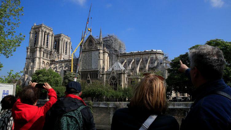 Des passants prennent en photo la cathédrale Notre-Dame de Paris et des ouvriers au travail, le 29 avril 2019, deux semaines après l'incendie qui a détruit la voute et la flèche de l'édifice. (GONZALO FUENTES / REUTERS)