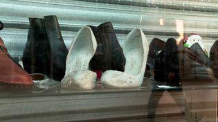 Des chaussures en béton au milieu des chaussures en cuir exposées dans une vitrine du centre-ville de Montpellier (France 3 Occitanie)