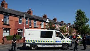 Des policiers britanniques bloquent l'accès à un site perquisitionné sur Dorset Avenue, dans le quartier de Moss Side à Manchester(Royaume-Uni), le 26 mai 2017. (OLI SCARFF / AFP)
