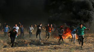 Des Palestiniens courent, lors d'une manifestation à Gaza, le 28 septembre 2018. (MAJDI FATHI / NURPHOTO / AFP)