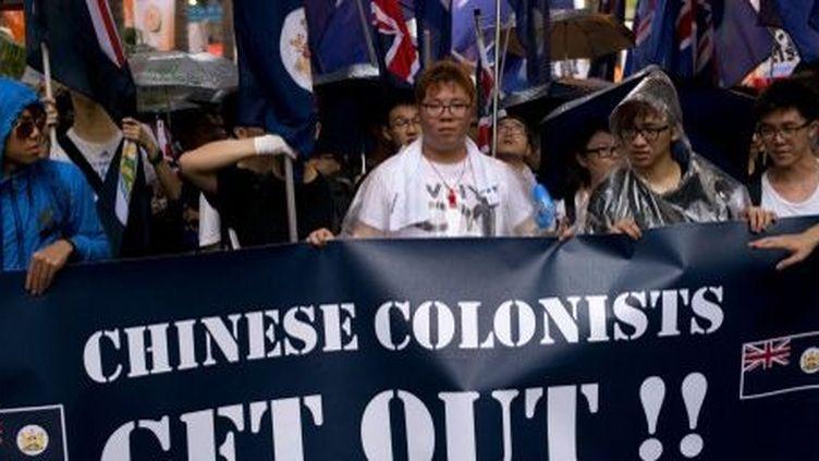Hong Kong, le 1er juillet 2013. Le ralliement pour la démocratie défile avec des drapeaux britanniques et une bannière qui annonce la couleur: «Colons chinois, dehors»... (AFP PHOTO / ALEX OGLE)