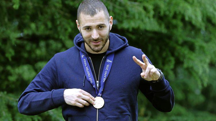 L'attaquant français Karim Benzema, avec sa médaille de vainqueur de la Ligue des Champions, le 31 mai 2015 à Lyon (Rhône), première étape de ses vacances passées loin de l'Euro. (RAFA CASAL / MARCA / SIPA)