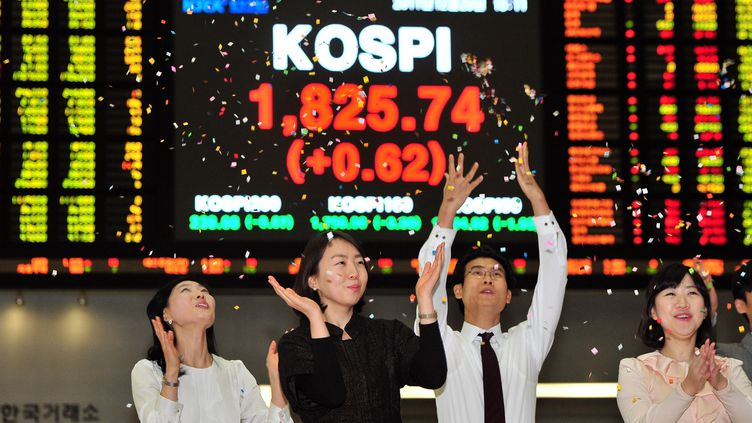 Des employés fêtent le dernier jour d'activité de l'année de la Bourse de Séoul (Corée du Sud), le 29 décembre 2011. (JUNG YEON-JE / AFP)