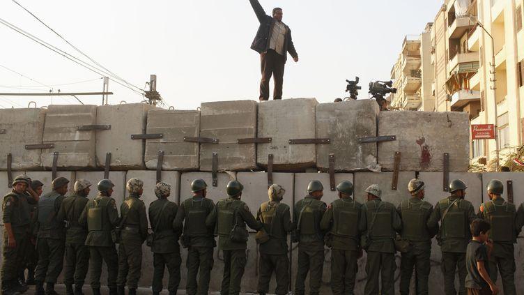 Un opposant à Mohamed Morsi s'exprime au Caire (Egypte), devant une colonne de soldats, le 9 décembre 2012. (ASMAA WAGUIH / REUTERS)
