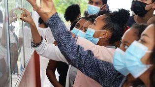 Des étudiantsregardent s'ils ont obtenu le baccalauréat à Saint-Denis (La Réunion) le 6 juillet 2021. (RICHARD BOUHET / AFP)