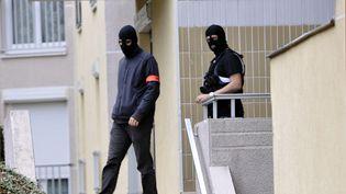 Des policiers quittent un immeuble où des box ont pu être utilisés par des membres de la cellule islamiste démantelée, le 10 octobre 2012 à Torcy (Seine-et-Marne). (MEHDI FEDOUACH / AFP)