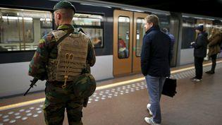 Un soldat belge et un homme qui prend le métro le 25 novembre 2015 à Bruxelles (Belgique). (BENOIT TESSIER / REUTERS)