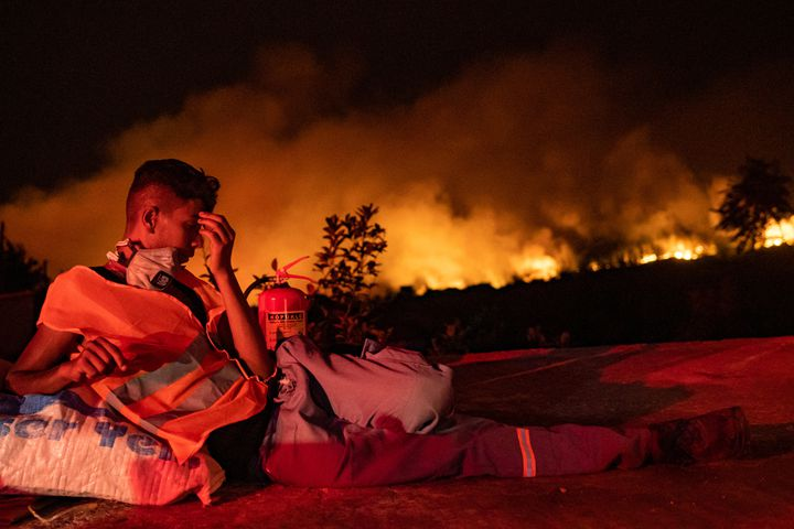 Un volontaire se repose alors que les flammes s'élèvent d'une forêt qui brûle en arrière-plan près d'Akcayaka, une ville de la province de Mugla (Turquie), le 6 août 2021. (YASIN AKGUL / AFP)