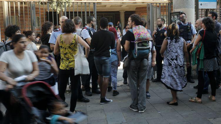 Des policiers catalans appartenant aux Mossos d'Esquadra gardent l'entrée d'une école où doit avoir lieu le scrutin, à Barcelone, le 29 septembre 2017. (PAU BARRENA / AFP)