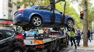 Des agents de la préfecture de Paris dressent une contravention, pendant qu'un véhicule est enlevé, le 16 septembre 2013. (  MAXPPP)