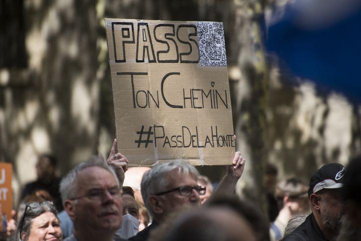 Une personnebrandit une pancarte pour marquer son opposition au pass sanitaire lors d'une manifestation organisée par Les Patriotes de Florian Philippot, le 7 août 2021, à Paris. (MAGALI COHEN / HANS LUCAS AFP)