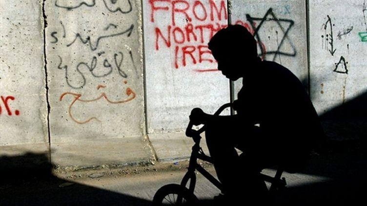 Un jeune cycliste palestinien devant le mur de séparation entre Jérusalem Ouest et Est (© AFP - Menahem Kahana)
