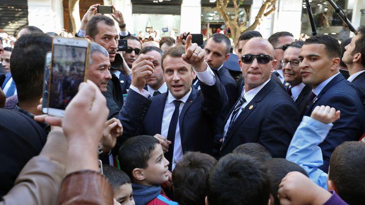 Le président français, Emmanuel Macron, entouré de gardes de sécurité, dans une rue d'Alger le 6 décembre 2017. (LUDOVIC MARIN / AFP)