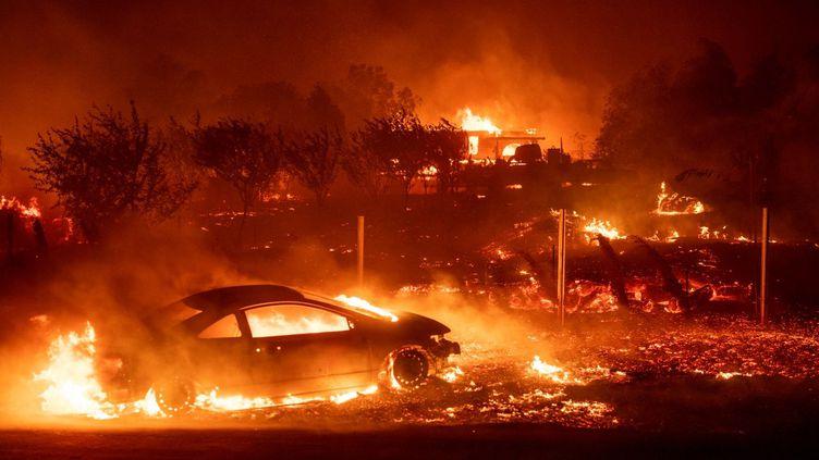 Une voiture et des maisons brûlent dans la ville de Paradise (Californie), aux Etats-Unis, le 8 novembre 2018. (JOSH EDELSON / AFP)