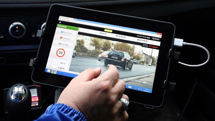 Un gendarme utilise un radar embarqué pour contrôler la vitesse d'un véhicule, le 13 juin 2013 à Saint-André-de-Cubzac (Gironde). (NICOLAS TUCAT / AFP)