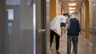 Le résident d'un Ehpad marche dans les couloirs, aidé d'une soignante, le 16 avril 2020 dans le Doubs. (SEBASTIEN BOZON / AFP)