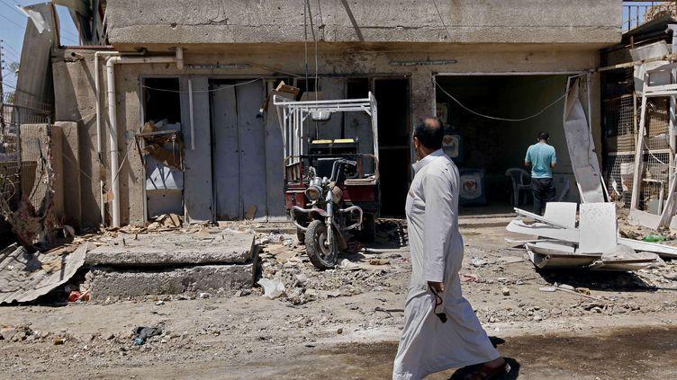 Des civils inspectent les dégats après une attaque à la voiture piégée près de Bagdad, le 25 avril 2013. (HADI MIZBAN / AP / SIPA)