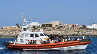 Des migrants venus de Tunisie et de Libye arrivent au large de Lampedusa (Italie) sur un bateau des gardes-côtes italiens, le 1er août 2020. (ALBERTO PIZZOLI / AFP)