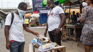 Un vendeur de masques dans une rue d'Accra, la capitale ghanéenne, le 20 avril 2020. (NIPAH DENNIS / AFP)