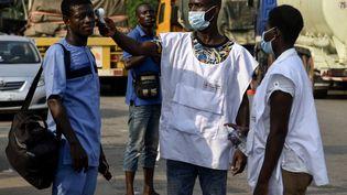 Deux employés de l'Institut national d'hygiène publique (INHP) vérifient la température des habitants d'Abidjan en Côte d'Ivoire, le 30 mars 2020 (photo d'illustration). (SIA KAMBOU / AFP)
