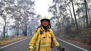 Un pompier volontaire surveille les feux de brousse dans la zone résidentielle de Dargan, à 120 kilomètres de Sydney, le 18 décembre 2019. (SAEED KHAN / AFP)