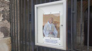 Le portrait de Jacques Hamel est affiché devant l'église de Saint-Etienne-du-Rouvray. (JULIETTE DUCLOS / FRANCETV INFO)