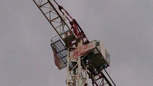La banderole d'Estelle Ast, mère d'un enfant autiste, grimpée en haut d'une grue de Toulouse, le 21 mars 2014. (MATHILDE LABAN / FRANCE 3 MIDI-PYRÉNÉES)