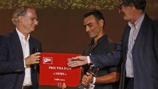 """Le photographe grec Aris Messinis (AFP) reçoit le Visa d'or """"News"""" à Perpignan des mains d'Olivier Royan (à gauche) et de Jean-François Leroy (à droite)  (Raymond Roig / AFP)"""