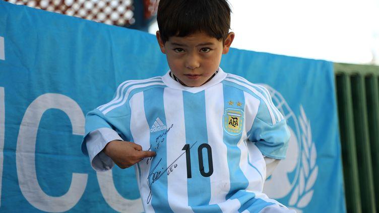 Murtaza, garçon afghan de 5 ans, fan de Lionel Messi, montre la signature de son idole sur le maillot argentin que le joueur lui a dédicacé, le 25 février 2016 à Kaboul (Afghanistan). (MAHDY MEHRAEEN / UNICEF AFGHANISTAN / AFP)