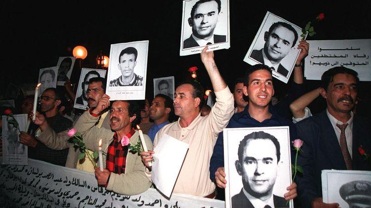 Des Marocains brandissent le portrait de Mehdi Ben Barka lors d'une manifesation le 29 octobre 2002 à Rabat, au Maroc, pour commémorer le 42e anniversaire de l'enlèvement de l'opposant marocain.