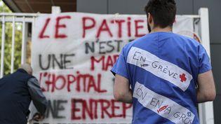 Un soignant de l'AP-HP en grève, le 15 avril 2019, à l'hôpitalde laPitié-Salpêtrière, à Paris. (KENZO TRIBOUILLARD / AFP)