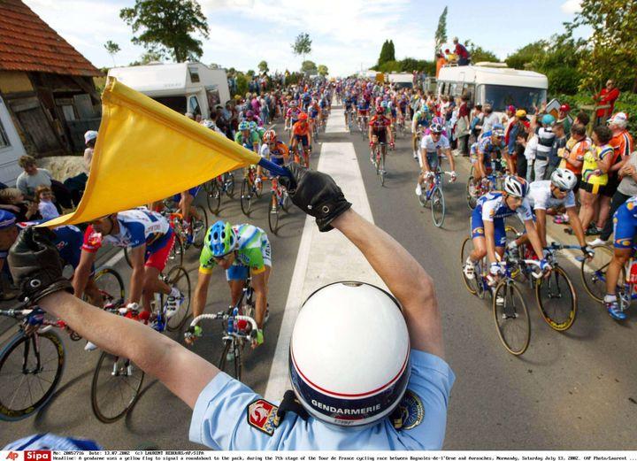 Un gendarme indique la présence d'un rond-point aux coureurs du Tour de France 2002, lors de la 13e étape entre Bagnoles-de-l'Orne (Orne) et Avranches (Manche), le 13 juillet 2002. (LAURENT REBOURS/AP/SIPA / AP)