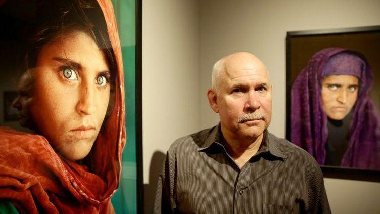 Le photographe américain Steve McCurry pose à côté des clichés qu'il a pris de Sharbat Gula, lors de l'exposition «Overwhelmed by Life» àHambourg, le 27 juin 2013. (ULRICH PERREY / DPA / AFP)