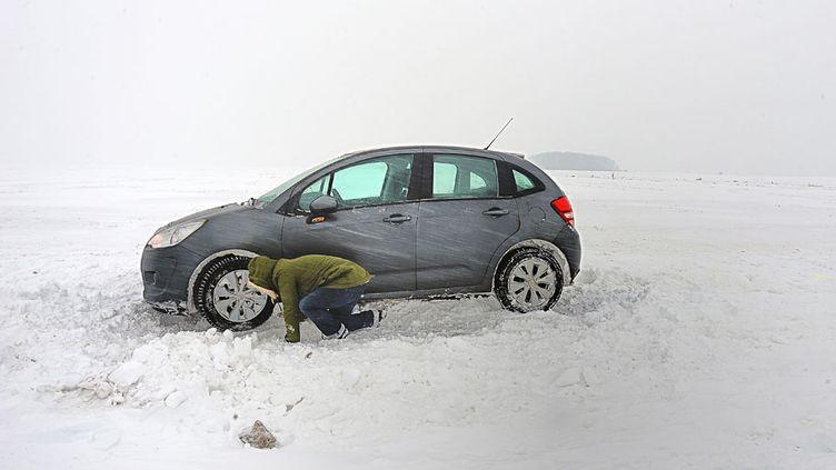 Clery-sur-Somme (Somme) - Un automobiliste tente de faire démarrer sa voiture bloquée par la neige, le 20 janvier 2013. (PHILIPPE HUGUEN / AFP)