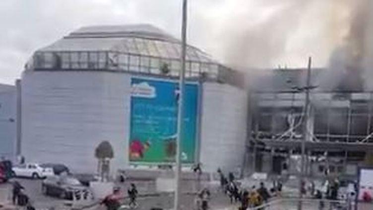 Capture d'écran d'une vidéo montrant de la fumée qui s'échappe de l'aéroport international de Bruxelles (Belgique), le 22 mars 2016. (ANNA AHRONHEIM / TWITTER)