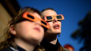 Une femme et une petite fille observent une éclipse, à l'Observatoire de Sydney (Australie), le 10 mai 2013. (SAEED KHAN / AFP)