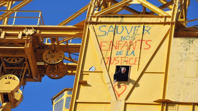 Serge Charnay, le père d'un enfant retranché en haut d'une grue à Nantes, vient de tagguer l'engin, le 17 février 2013. (FRANK PERRY / AFP)