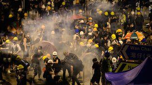 Des opposants au gouvernement hongkongais sous un nuage de gaz lacrymogène, mardi 2 juillet 2019 au matin non loin du Parlement de la mégalopole. (ANTHONY WALLACE / AFP)