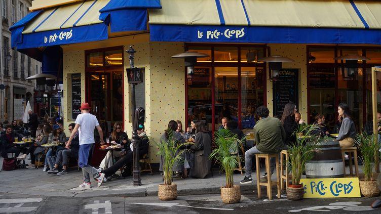 Des clients sont assis à une terrasse de café, à Paris, le 21 mai 2021. (MYRIAM TIRLER / HANS LUCAS / AFP)
