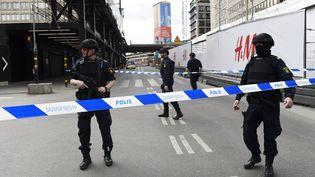 Des policiers dressent un cordon de sécurité autour du lieu où un camion s'est encastré dans un magasin, le 7 avril 2017, dans le centre-ville de Stockholm (Suède). (JONATHAN NACKSTRAND / AFP)