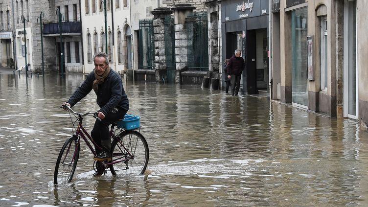 Un cycliste dans une rue inondée de Ornans, dans le Doubs, le 23 janvier 2018. (SEBASTIEN BOZON / AFP)