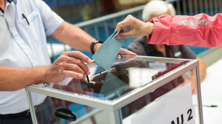 Une femme vote, au premier tour des élections régionales, en Occitanie, le 20 juin 2021. (MATTHIEU RONDEL / HANS LUCAS / AFP)